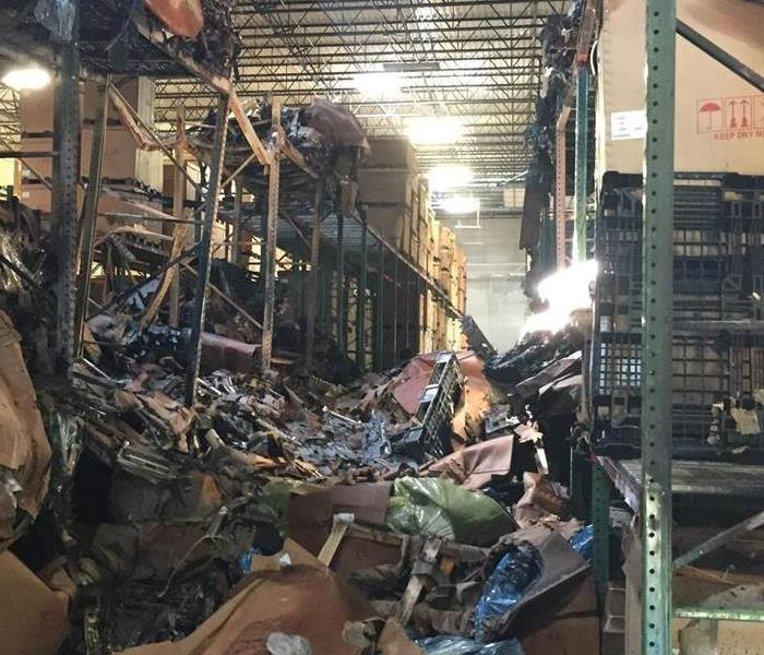 Warehouse destroyed and boxes are a mess on the ground from a large water loss.