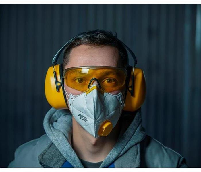 A man wearing yellow headphones for ear protection, goggles and an air-purifying mask